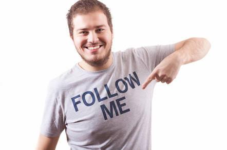 Guy pointing at a shirt reading 'Follow me'