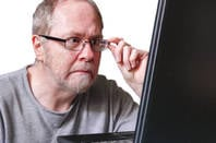 Man possibly shocked at what he's seeing on computer screen