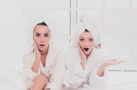 women in bathrobes look shocked