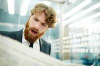 man shocked when reading newspaper
