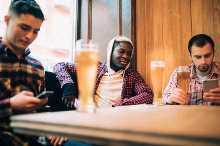 Men drink beer, play with cellphones / mobile phones