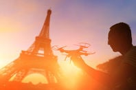 Man preps drone to fly over eiffel tower, in paris, france.