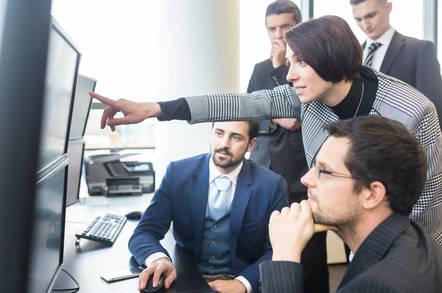 team of office workers peers at multiple monitors