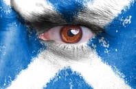 Angry man's eye peers from face painted with Scottish flag / st andrews cross