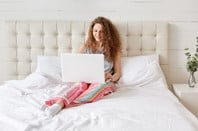 Woman sits in bed and works on laptop in her home.