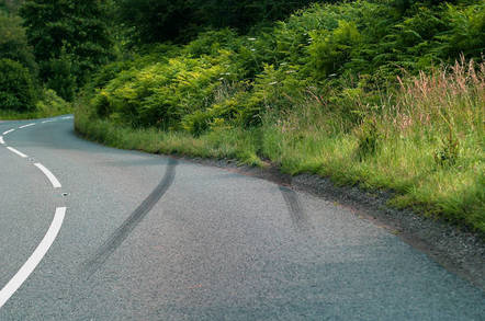 car crash skid marks on a rural road heading into the undergrowth