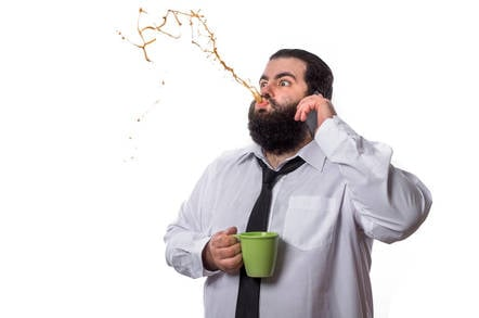 A man spits out his coffee