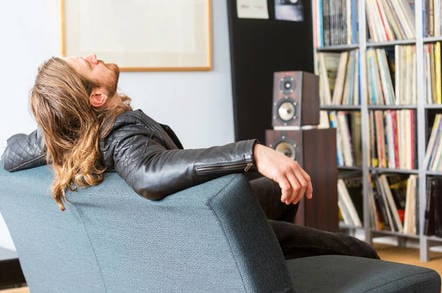 An audiophile leaning back on a couch listening to music
