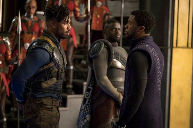Marvel Studios' BLACK PANTHER..L to R: Erik Killmonger (Michael B. Jordan) and T'Challa/Black Panther (Chadwick Boseman), b/g W'Kabi (Daniel Kaluuya)..Photo: Matt Kennedy..©Marvel Studios 2018