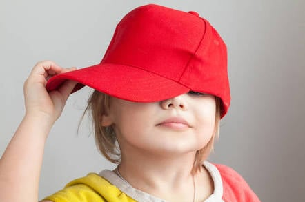 Studio portrait of funny baby girl in red baseball cap over gray wall background