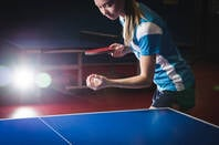 Woman serves in ping pong game