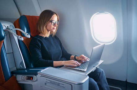 young business woman working on laptop computer while sitting in airplane