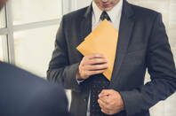 Man in suit sticks brown paper envelope in jacket