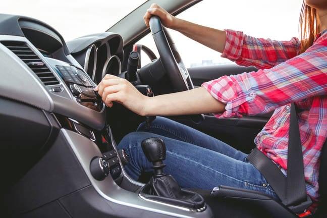 woman adjusts digital car radio