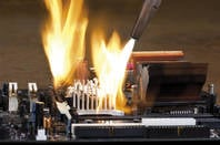 A blowtorch burning a computer board
