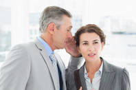 business guy whispers something to his unimpressed colleague