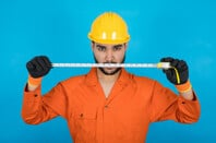 Repairman in orange overalls threateningly wields tape measure