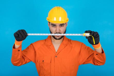 Repairman in orange overalls threateningly wields tape measure