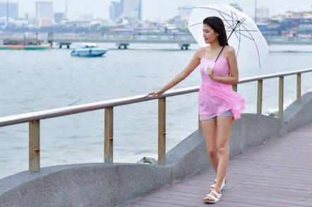 A woman walking in the rain by water