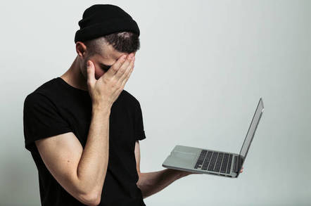 Young guy facepalms while holding a laptop