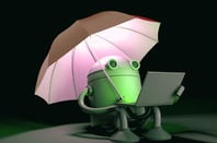 Android robot sitting under an umbrella on its laptop in the dark