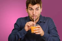 Man drinks juice through straw