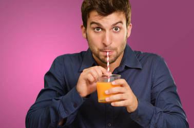 Man drinks juice through straw