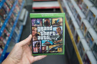 Man holding Grand Theft Auto disk Editorial Use Only
