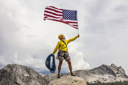 Climber waves an American Flag from the summit after a challenging ascent