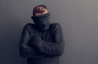 Young man covers face with jumper