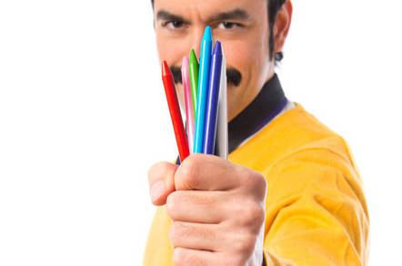 Man holds out fistful of  crayons