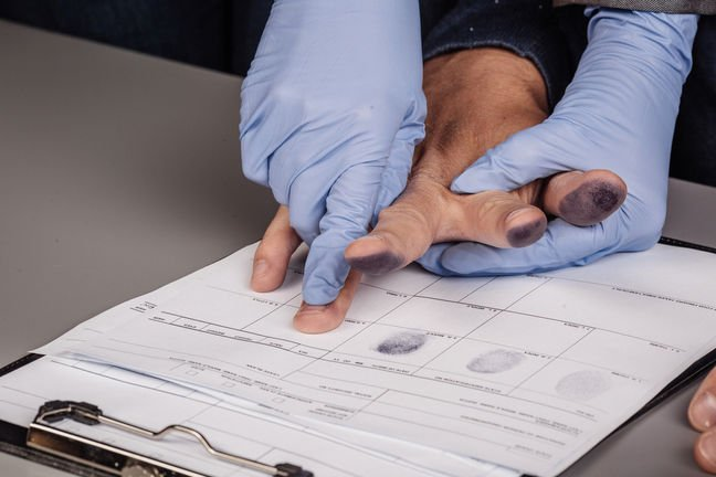 Blockchain: man gets fingerprinted by gloved person