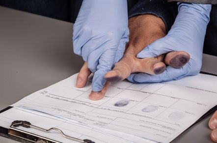 man gets fingerprinted by gloved person