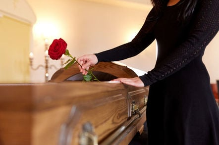 Woman with red roses and coffin at funeral in church