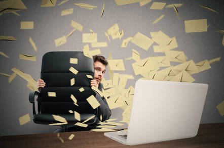 A man hiding from a lot of emails coming from a laptop