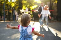 Child running to parents at park