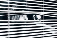 young woman looks through blinds