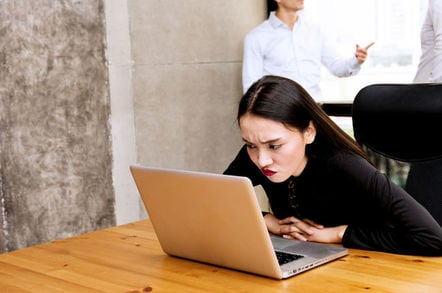 Woman looks irritated by background workers while on laptops