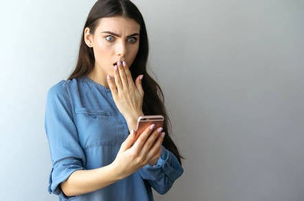 Someone looking at their smartphone shocked