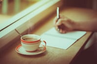 A coffee cup and hand writing in notebook
