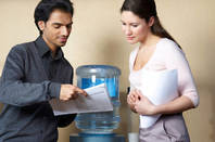 Two people standing talking by a water cooler