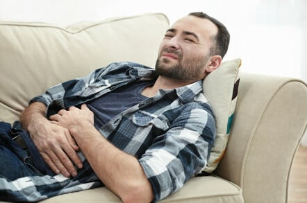 Man suffering from stomach ache while lying on sofa