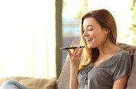 Woman talks into smartphone / cellphone with the device held flat