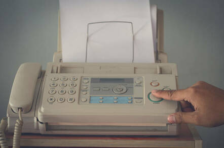 An old fax machine with someone pushing a button