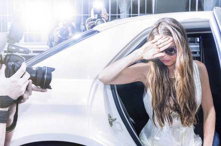 Celeb exits car while paparazzi try to take her picture
