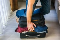 person sitting on suitcase to force it closed