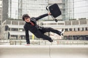Business man with suitcase jumping over urban obstacles