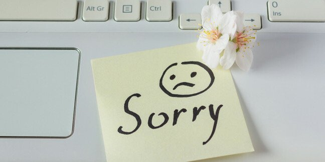 Handwritten note on keyboard saying sorry with sad face