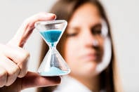 Someone holding an hourglass of blue sand