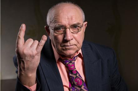 Elderly man making a horns gesture